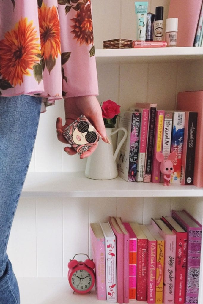 girl holding blusher in front of bookcase filled with pink books