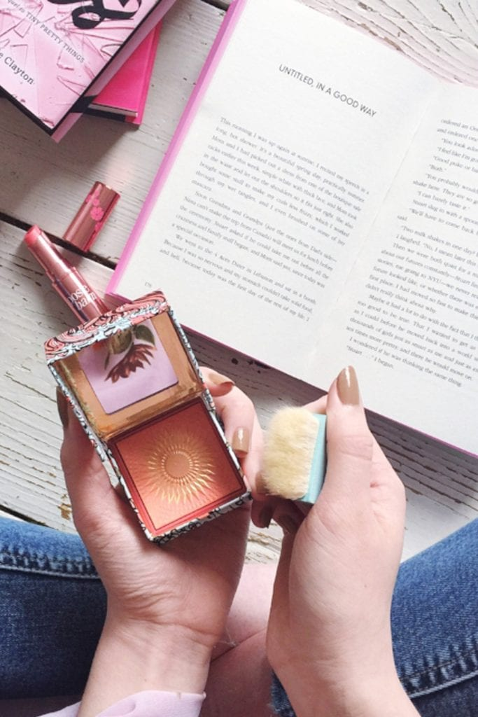 girl holding blusher and reading a book